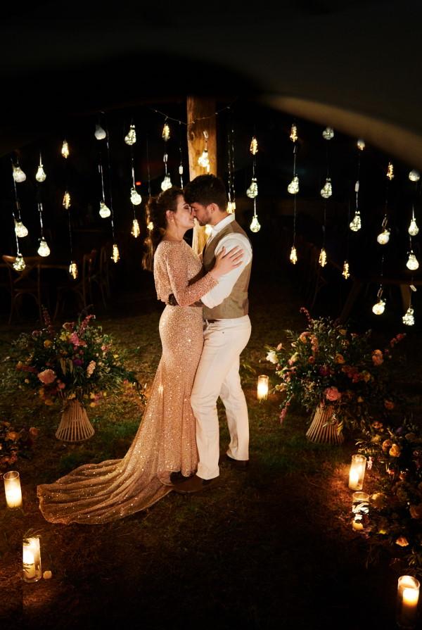 Bride and groom kiss in the dark of night under festoon lighting