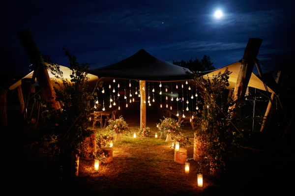 Hanging festoon lighting in the evening surrounded by candles by the Wedding Tents in the Lavender Meadows of Domaine de Bres