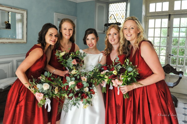 Bride with red lipstick and bridesmaids in red dresses for winter wedding