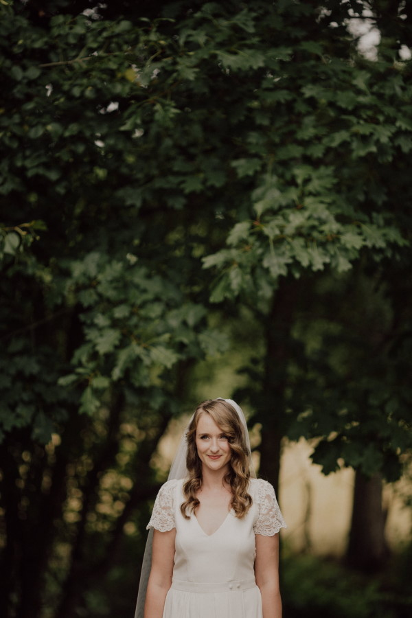 Bride in garden in moody bridal shoot with long curled hair for winter wedding