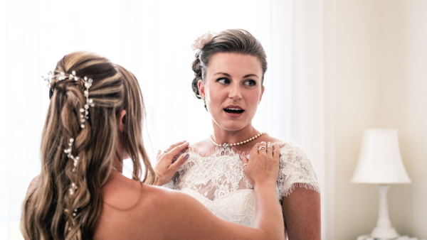 Bride with Pearl necklace and hair accessory gets ready for winter wedding