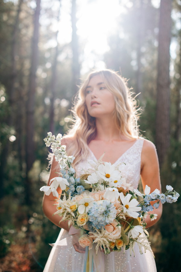 Bride holding bouquet in forest by the sea at Le Petit Nice