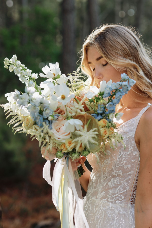 Dappled sunlit bride closes eyes and smells bouquet