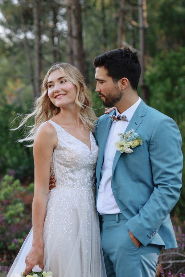 Groom in seafoam blue suit and bride smile in forest