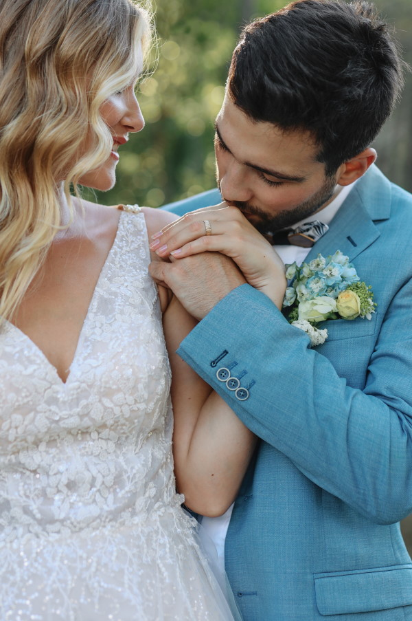 Upclose groom kisses brides hand in ocean themed wedding