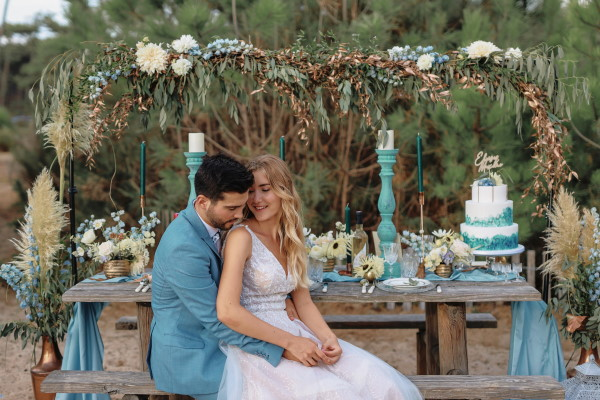 Couple in seated embrace by table at ocean wedding in Le Petit Nice