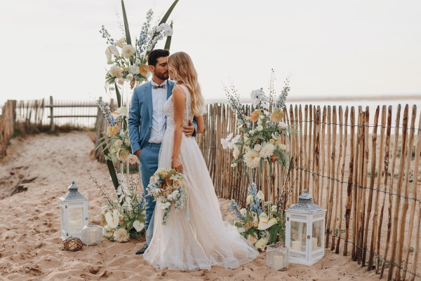 Beachside wedding ceremony with floral arbor and lanterns