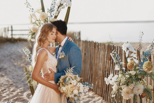 Couple kiss at beach wedding in afternoon sun groom in blue suit