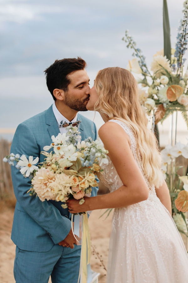 Couple in natural colours and blues kiss in beachside wedding in France