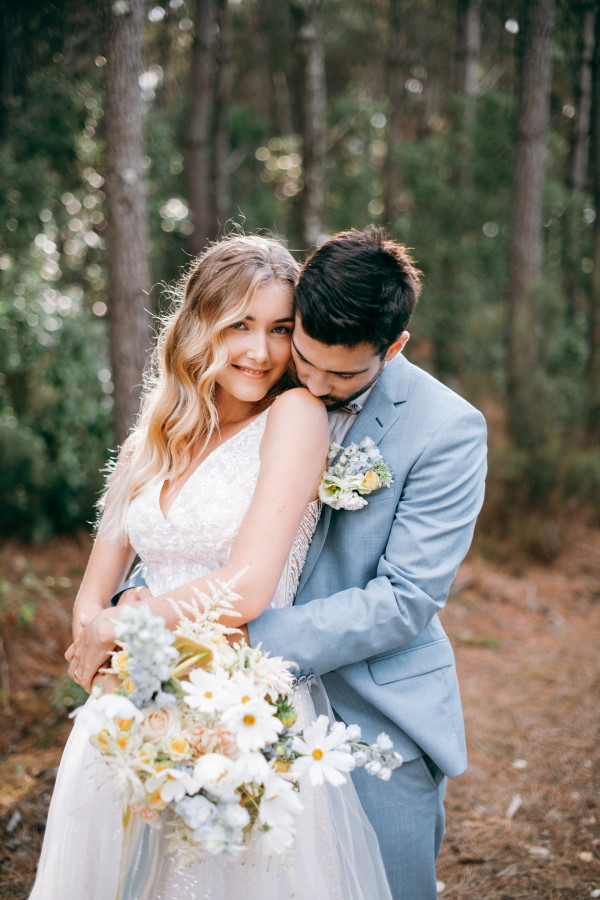 Bride and groom hug in forest wedding with ocean blue themed bouquet and suit