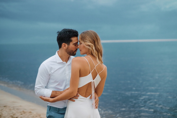 Groom in blue suit pants and bride in white silk open back gown by the sea
