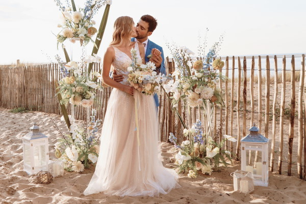 Sea side wedding ceremony in sunlight in sparkling gown and seafoam suit