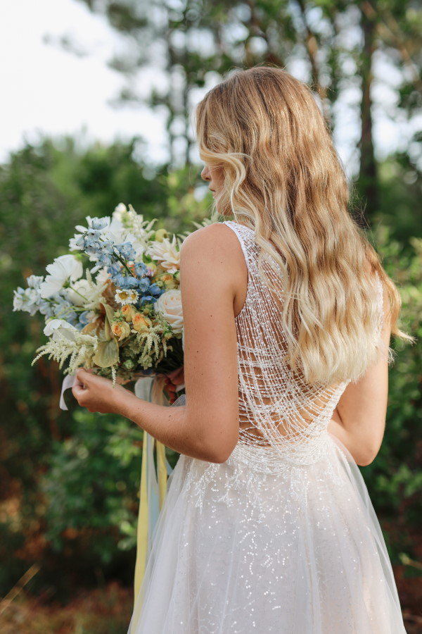 Bride with back to camera in beaded dress with sea blue themed bouquet
