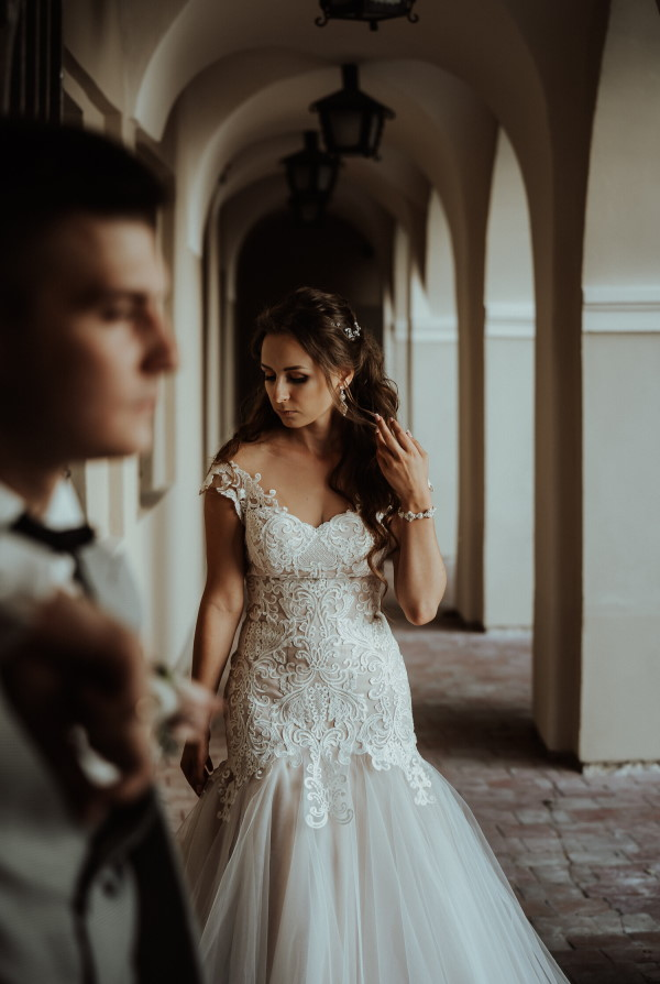 bride in wedding dress looks down at her bouquet with groom in foreground next to archways of old building