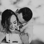 black and white image of groom with arms around brides neck from behind she is smiling