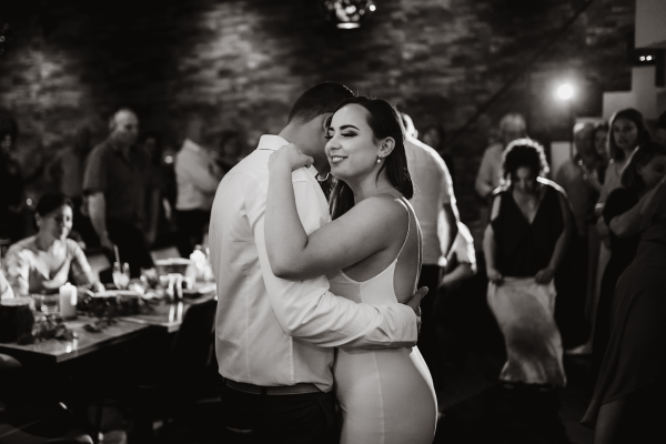 black and white image of bride dancing with groom she is smiling and his head is concealed behind hers
