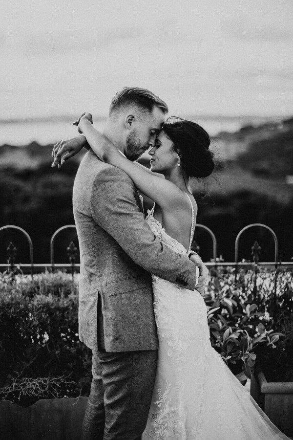 black and white image of bride with arms around grooms neck in a garden with a view