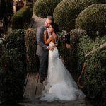 bride and groom stand amongst neatly cut round hedges she wears a long tulle gown they look into the distance