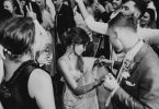 black and white image of bride dancing with groom she looks down and is holding his hand