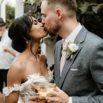 bride and groom kiss with eyes closed. bride in off shoulder lace gown and groom in grey suit holding champagne