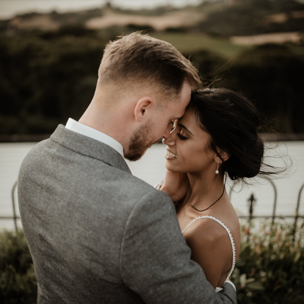 bride and groom touch heads with eyes closed with outdoor view behind them