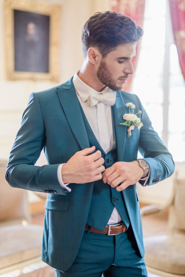 Groom gets ready and puts on blue suit jacket
