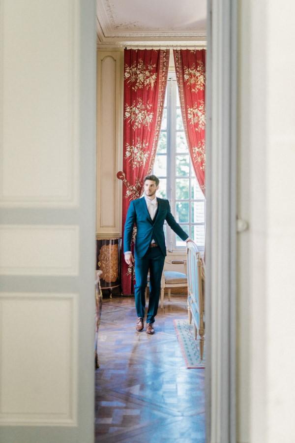 Groom walks down hallway of Chateau de Baronville in blue suit