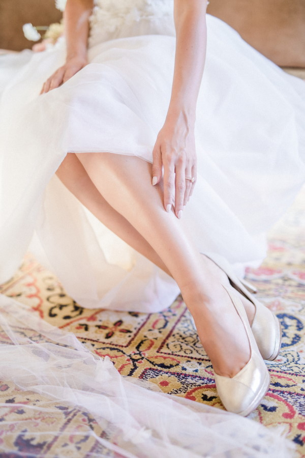 Close up of brides legs in gown and shoes