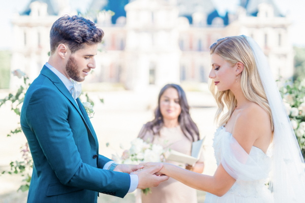 Bride and groom hold hands in front of celebrant in literary themed wedding