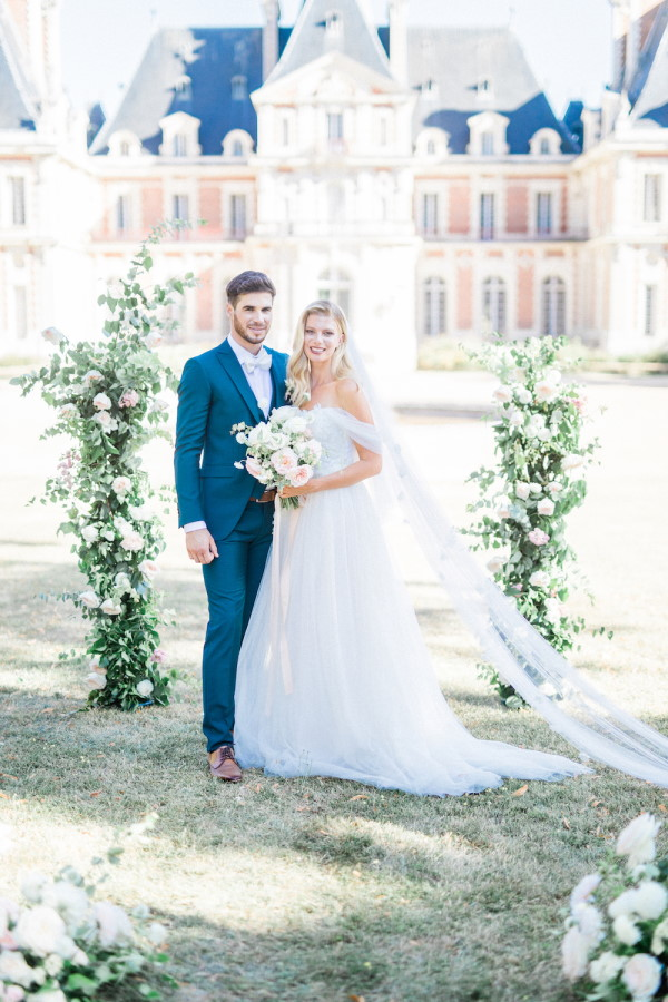 Bride and groom pose in front of white rose arbour outside Chateau de Baronville, France
