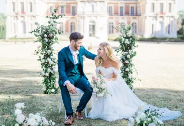 Couple seated by white rose arbor outside Chateau de Baronville France