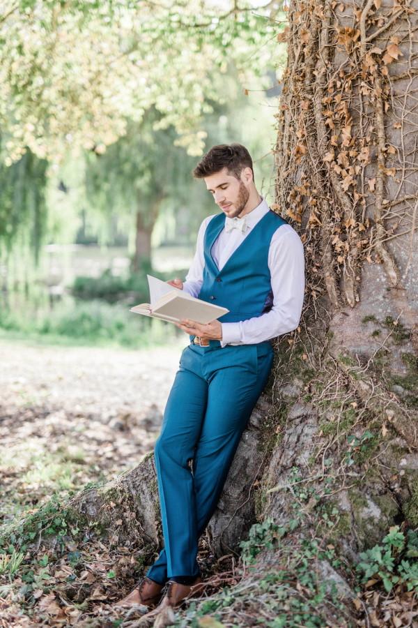 Groom in blue waistcoat reads under tree