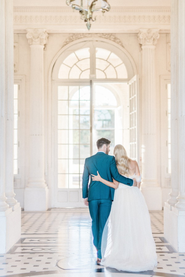 After literary wedding nuptials have finished the bride and groom walk the white halls of Chateau de Baronville arm in arm