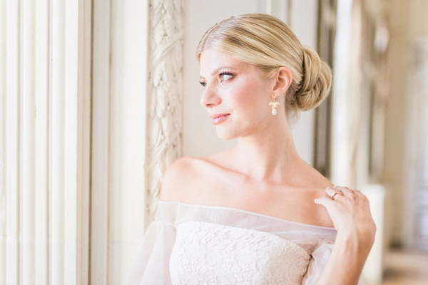Close up of bride with hair in bun and off shoulder white dress