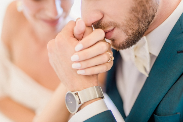 Close-up of groom in watch kissing brides hand