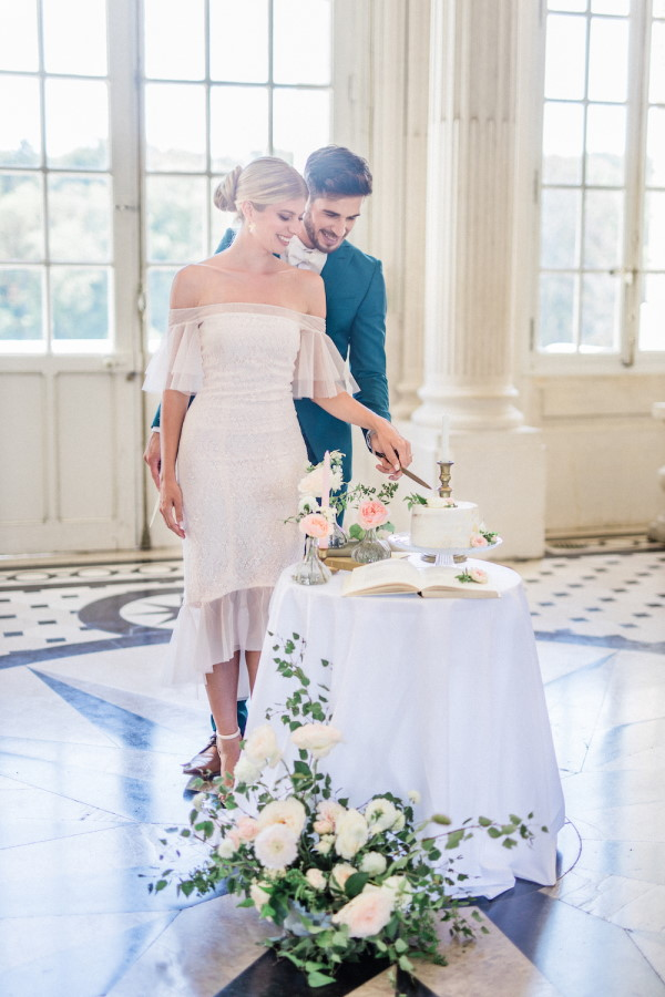 Bride and groom cut cake and stand together by windows in Chateau de Baronville France