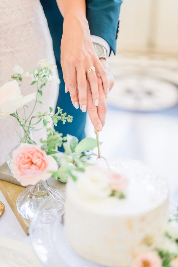 Closeup of bride and grooms hands cutting cake