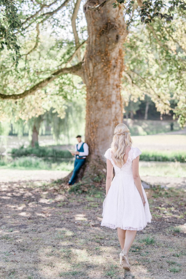 Bride in short white dress approaches groom in blue waistcoat reading under tree
