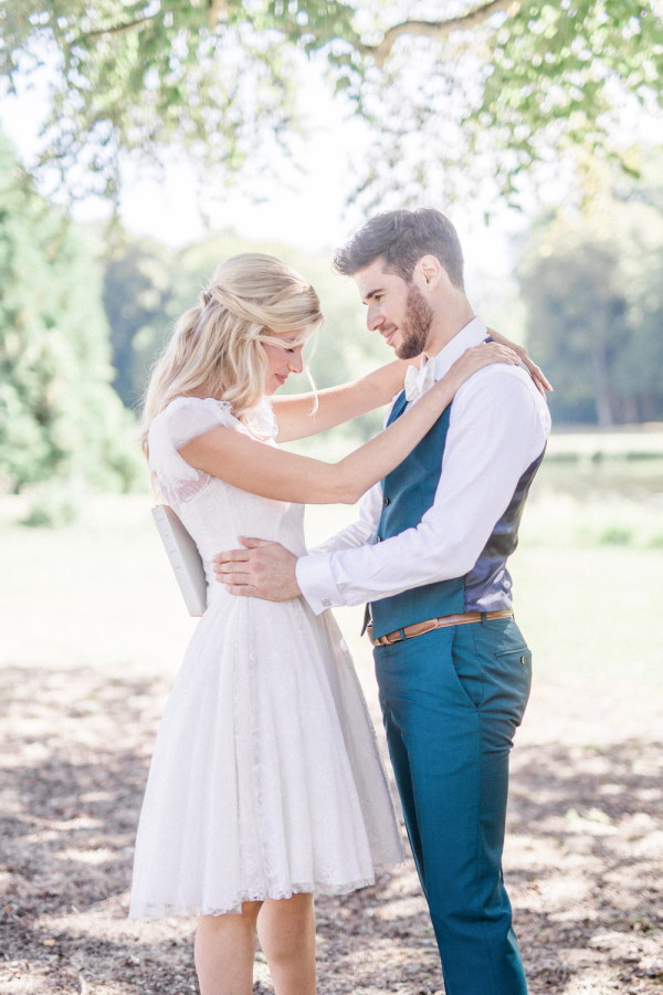 Bride in short white dress and groom in blue waistcoat embrace outdoors
