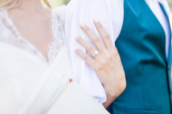 Closeup of brides hand with wedding ring holding arm of groom in blue waistcoat