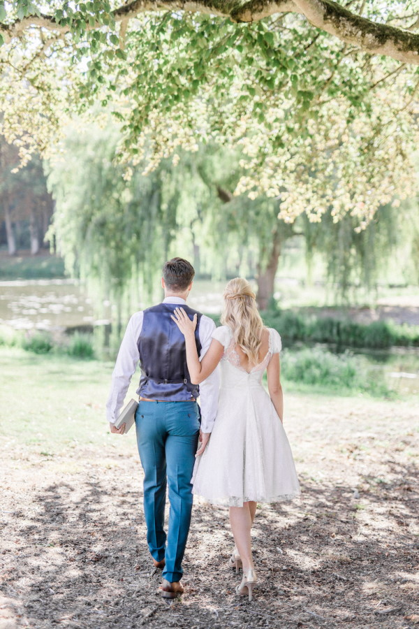 Bride and groom walk away from camera towards willow trees outdoors holding books