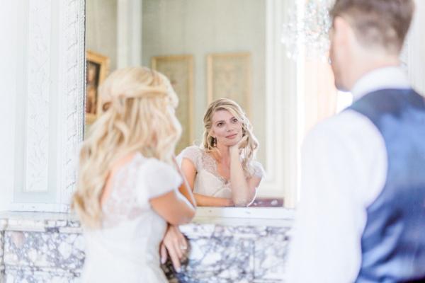 Groom in blue waistcoat looks at bride in mirror