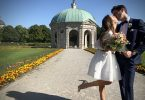 Bride and Groom kiss in front of aged green copper roofed building in garden