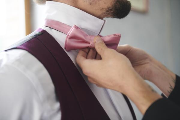 hands tie up pink bow tie for groom in purple suit