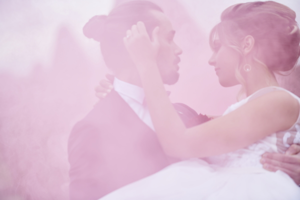 bride and groom just visible in each others arms through pink smoke haze
