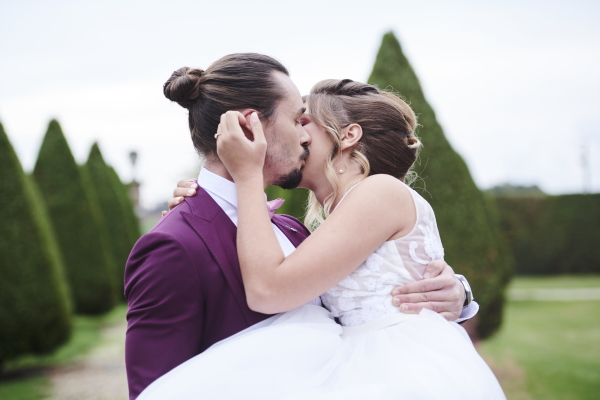 groom holds bride in his arms in manicured garden as they kiss each other