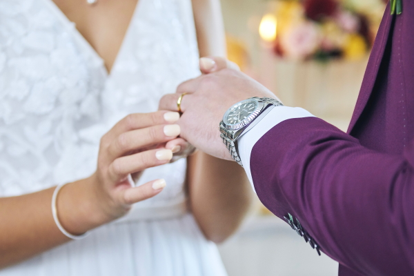 Bride places grooms ring on his finger who wears wristwatch on left hand