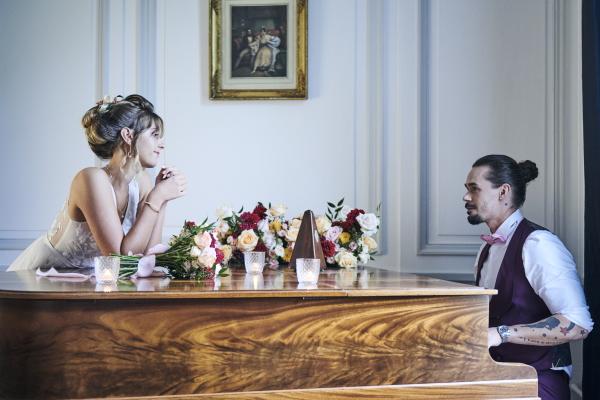 groom in purple waistcoast plays piano to his bride who leans on the piano