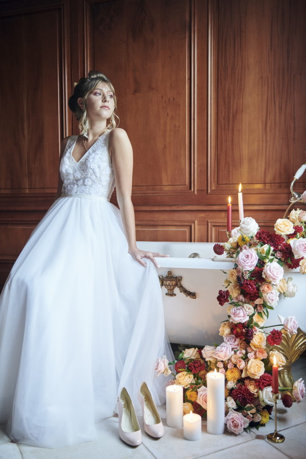 bride sits on edge of bathtub surrounded by flowers and candles in white lace gown