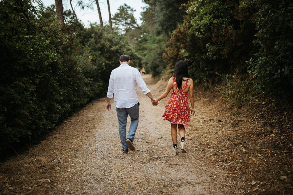 Couple walk hand in hand down gravel path with back to camera